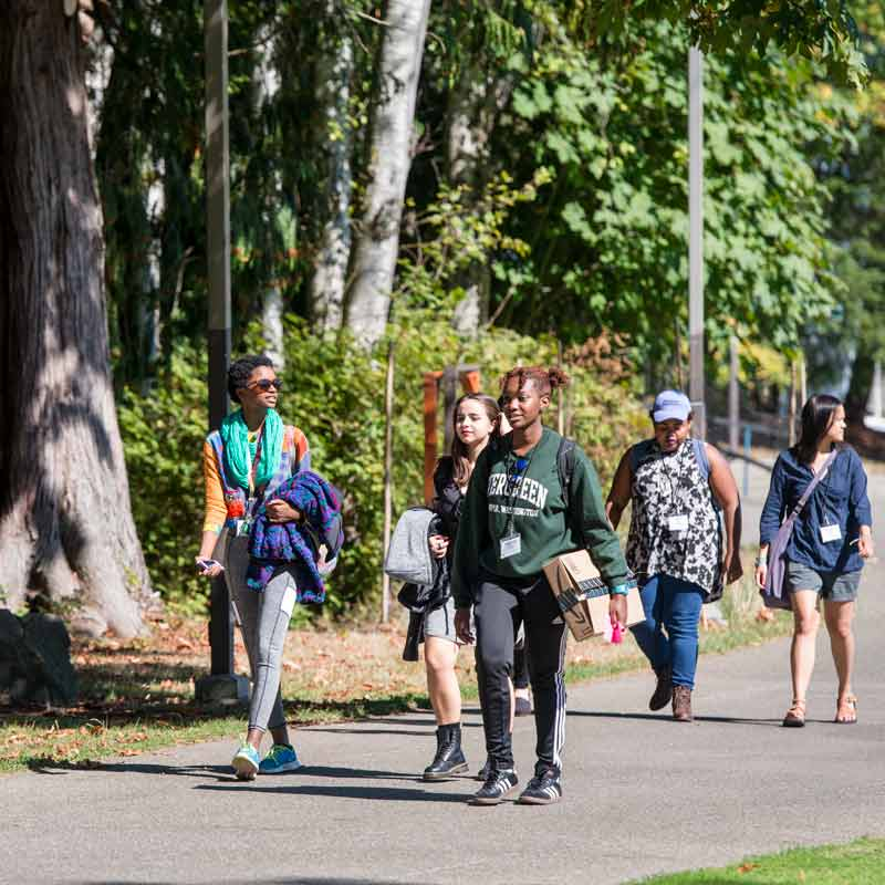 Background image of multicultural scholars walking throughout campus