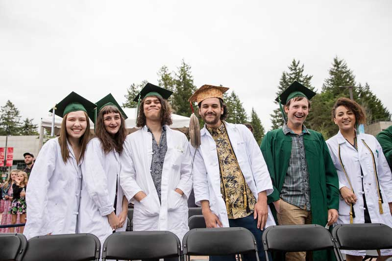 A line-up of Evergreen grads in white coats and green graduation caps smile for the camera.