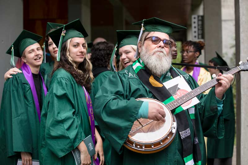 An older man with a bushy beard plays a banjo before other fellow graduates at Evergreen's 2019 commencement ceremony.