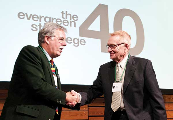 David Nicandri congratulates Richard Schwartz, right, during the college's 40th anniversary party.
