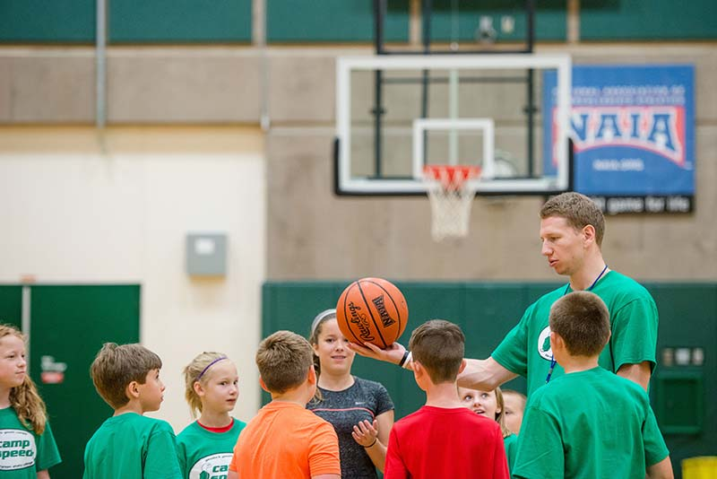 Camp Speedy Basketball children and adult holding ball