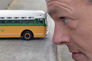 A model bus near a man's head.