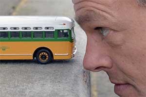 A model bus near a man's head.