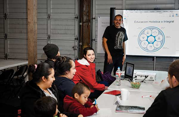 In a garage-turned-classroom, Melanie White '14 looks on as Eder Nuñez '17 leads a literacy info session.
