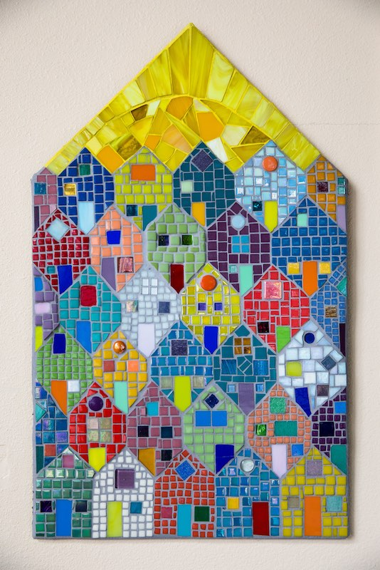 A tile mosaic piece made for a tiny house development made to house Olympia's homeless community hangs on the wall at Arbutus Folk School.