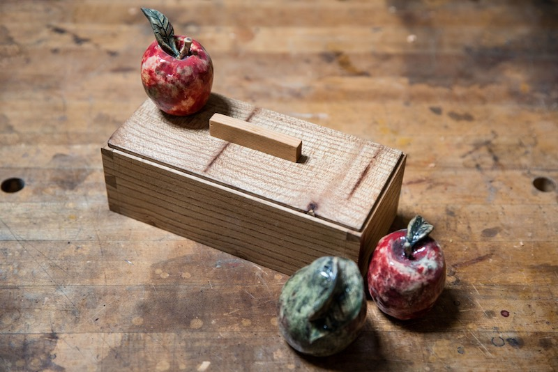A box made with local wood as a sample for a dovetail woodworking class along with ceramic miniature fruit at Arbutus Folk School.