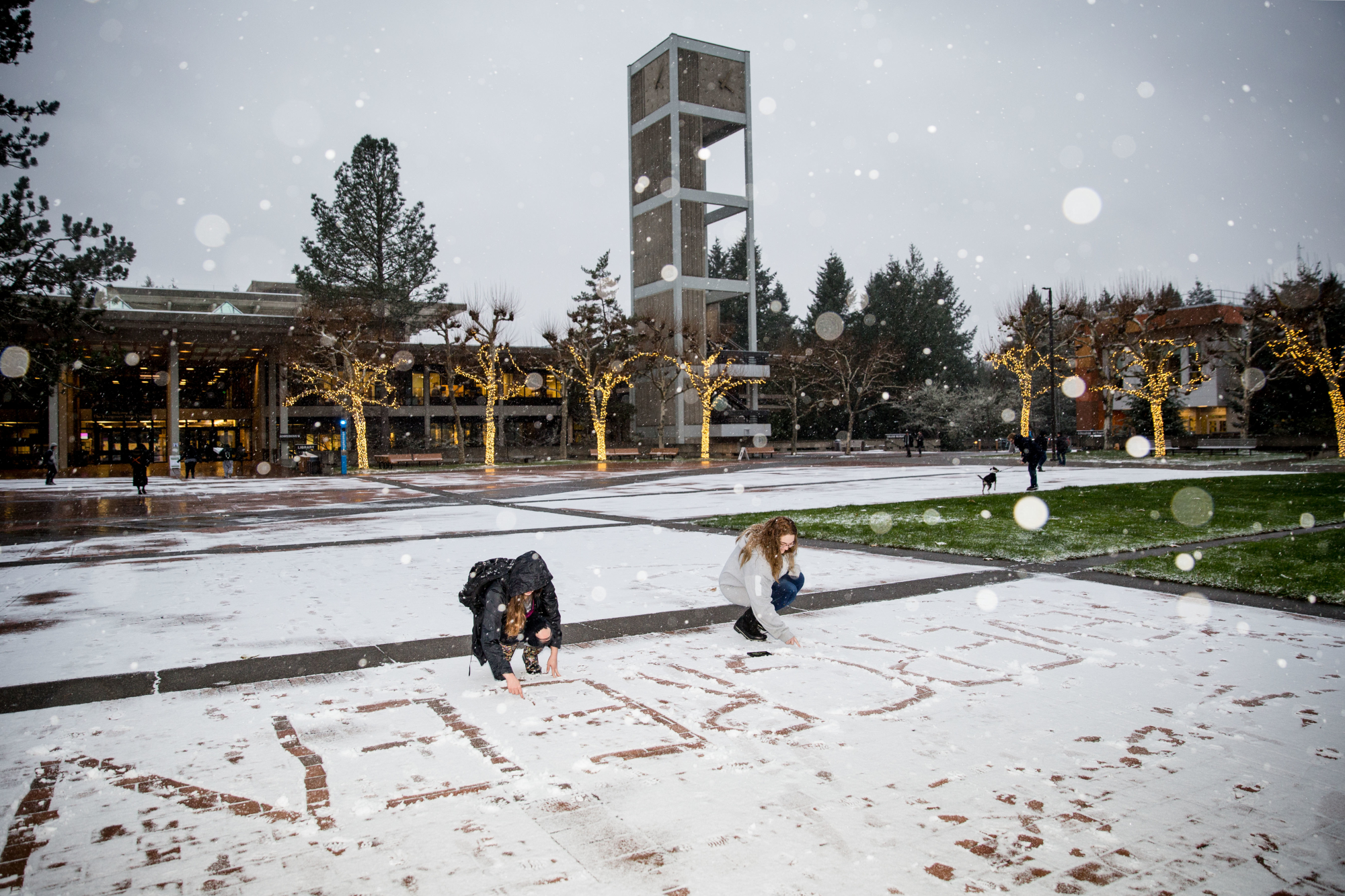 "Two students writing ""Evergreen"" in the snow on Red Square."