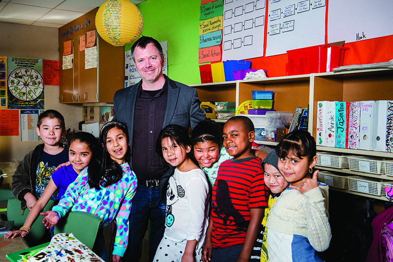 Ryan Reilly, MiT 2007, stands with eight of his elementary school students in a Seattle classroom.