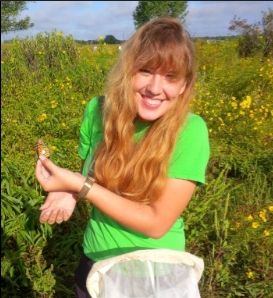 Woman in field holding butterfly, smiling