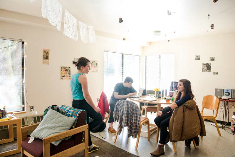 Three students hang out in their apartment common area
