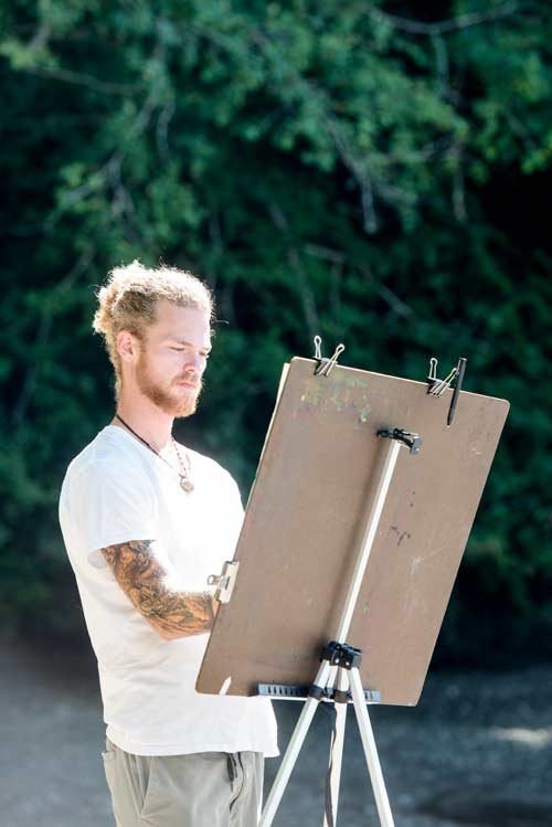 A student draws on an easel at Evergreen Beach during an open-air session.