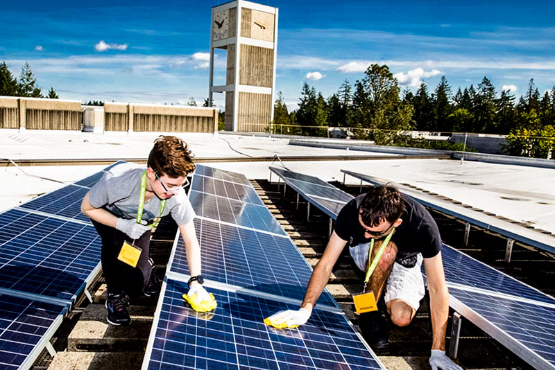 students cleaning solar panels