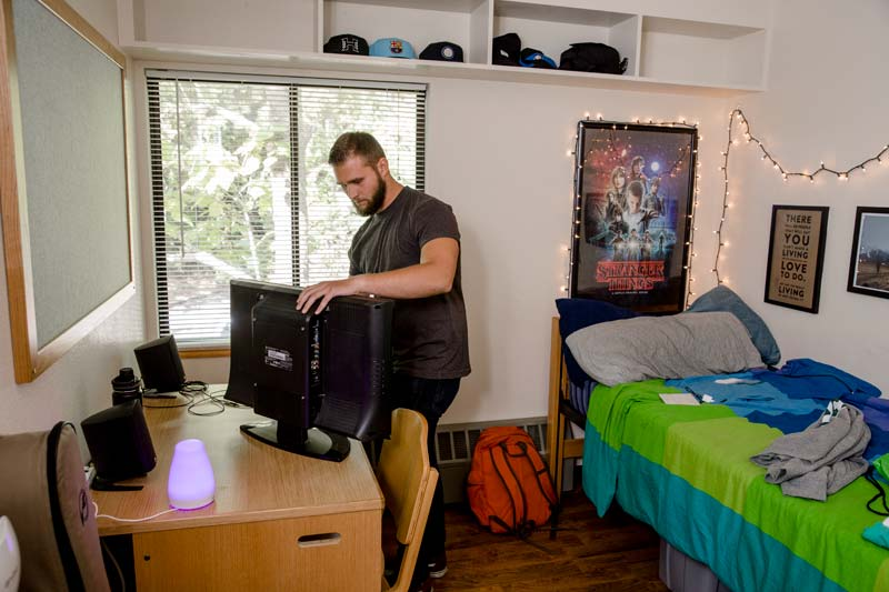 A student moves into his dorm room, hanging posters and setting up his computer