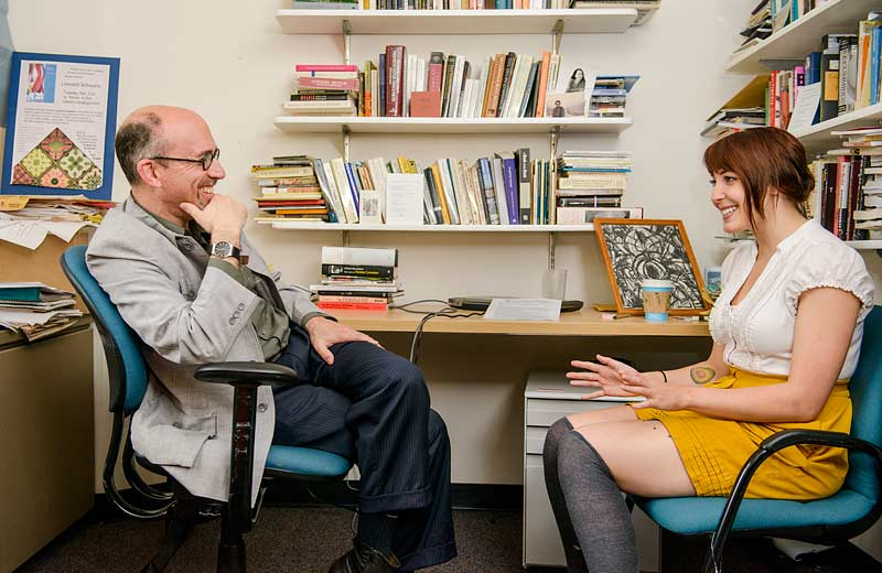 Faculty Leonard Schwartz converses with a student about her evaluation
