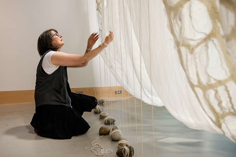 Textile artist and Evergreen alumna Janice Arnold installing a piece in the Evergreen Gallery for her one-woman show, Palace Yurt Deconstructed.