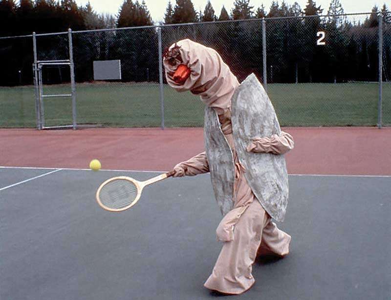 A performer plays tennis in a rustic, home-made Speedy mascot costume that features a duck beak and eyes at the end of a tall siphon