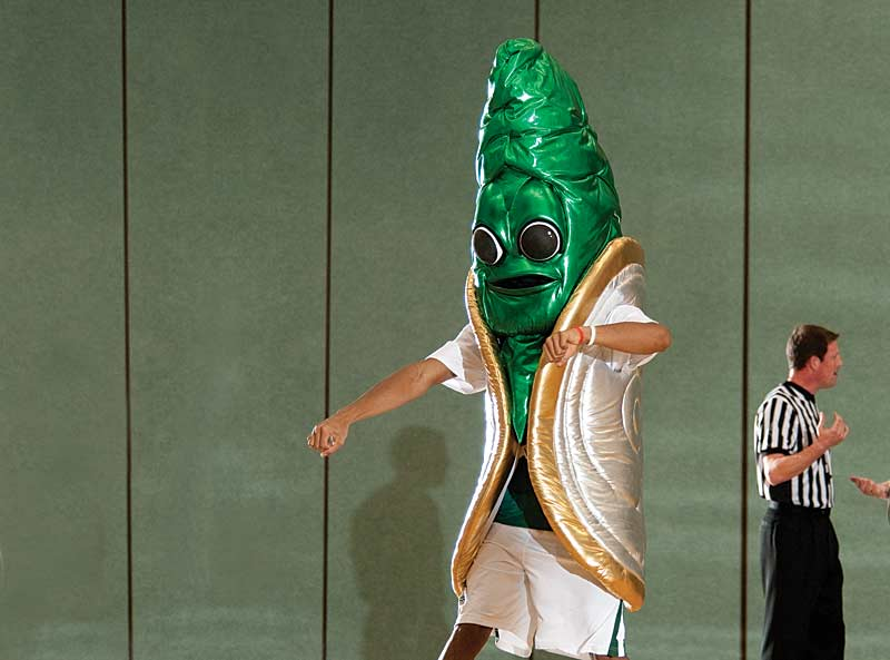A performer in a lamé costume with big, cartoon eyes, a ridged green siphon, and a gold-accented shell dances on a basketball court