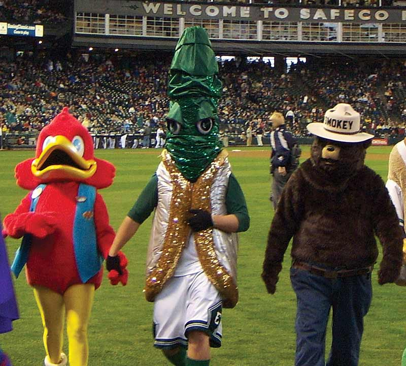 A performer in a glittery geoduck costume with a tall, green siphon and angry eyes walks on a baseball field with several other mascots