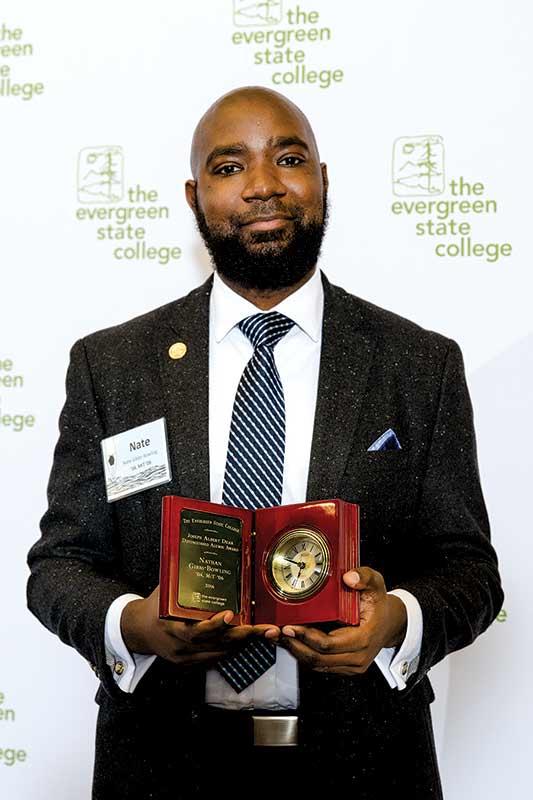 Nate Gibbs-Bowling holding the Joseph Albert Dear Distinguished Alumni Award.