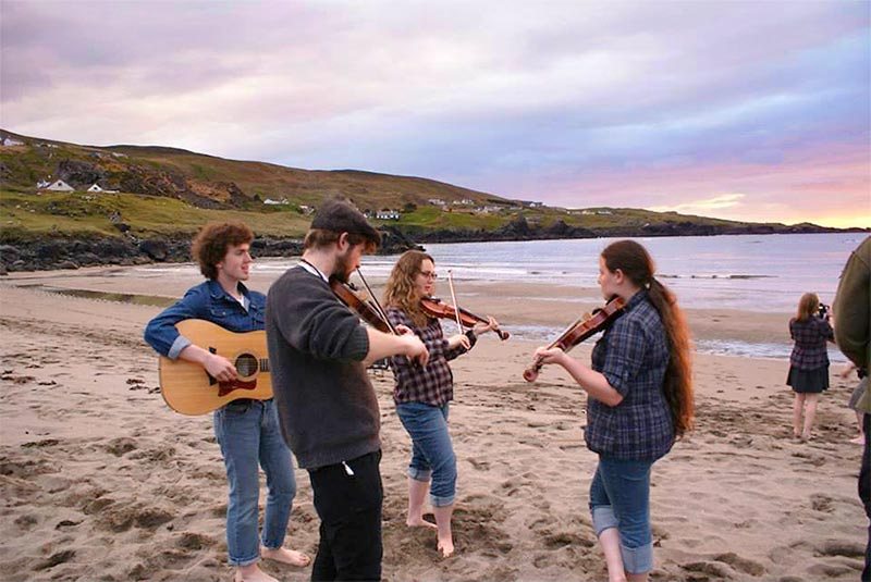 A group of Study Abroad students play music together during a sunset in Ireland.
