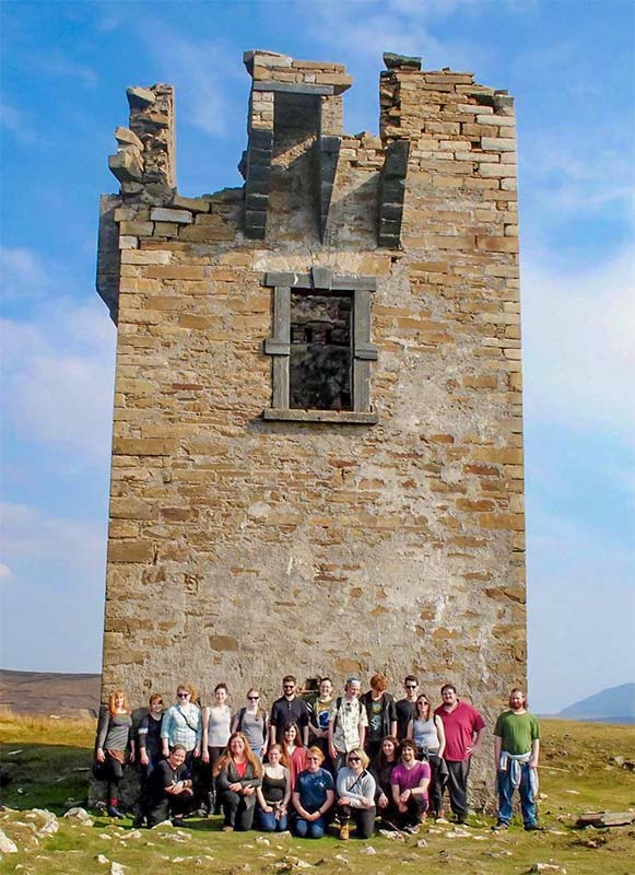 A group of Study Abroad students under an ancient tower in the Irish countryside.