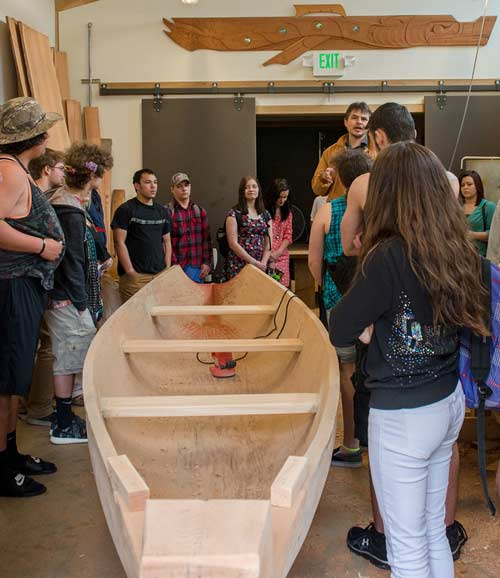 A photo of a boat with people standing around it, at the opening of the new carving studio.