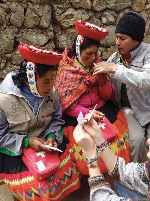 Matilde and Beatriz learn to use a digital thermometer with help from Ruben, a Quechua translator.