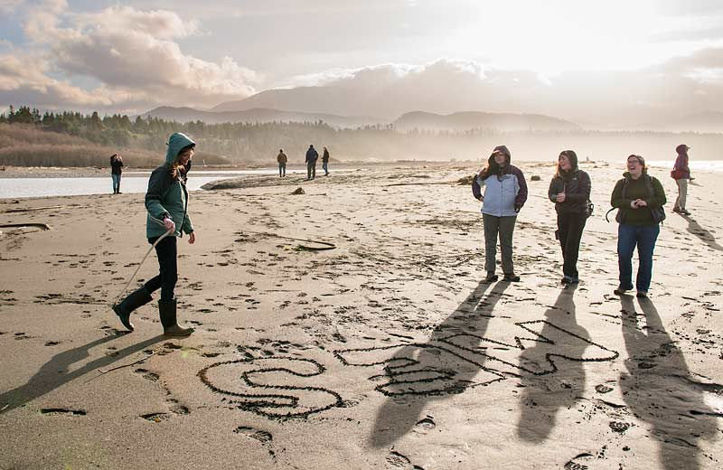 "Students scratch ""MES"" into the sand on a beach"