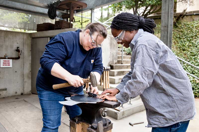Metalworking students work with casting, anvils, and grinders in the Arts Annex shops area.
