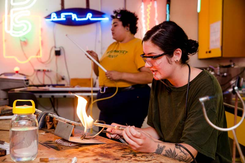 Students learn to shape glass into neon signs in the neon studio.