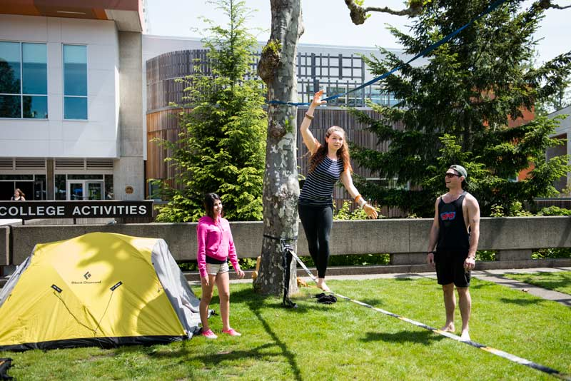 A student tries walking a slackline as two friends watch on
