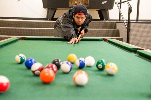A student plays a game of pool in the dorms
