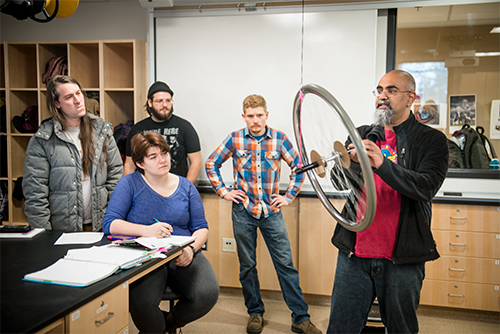 Students observing instructor Krishna Chowdary demonstrate how gyroscopes work using a bicycle wheel, and rope hanging from the celling.
