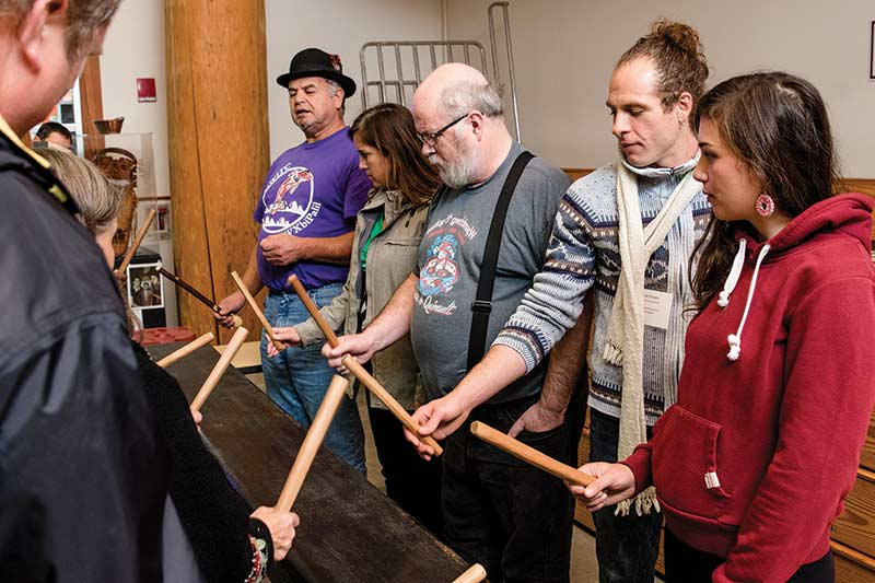 """Alumni try their hand at the drumming plank during the """"Engaging with Longhouse Art and Artists"""" session."""