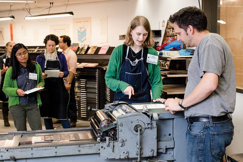 Book arts faculty member Steven Hendricks teaches participants how to create an Evergreen logo print with a letterpress.