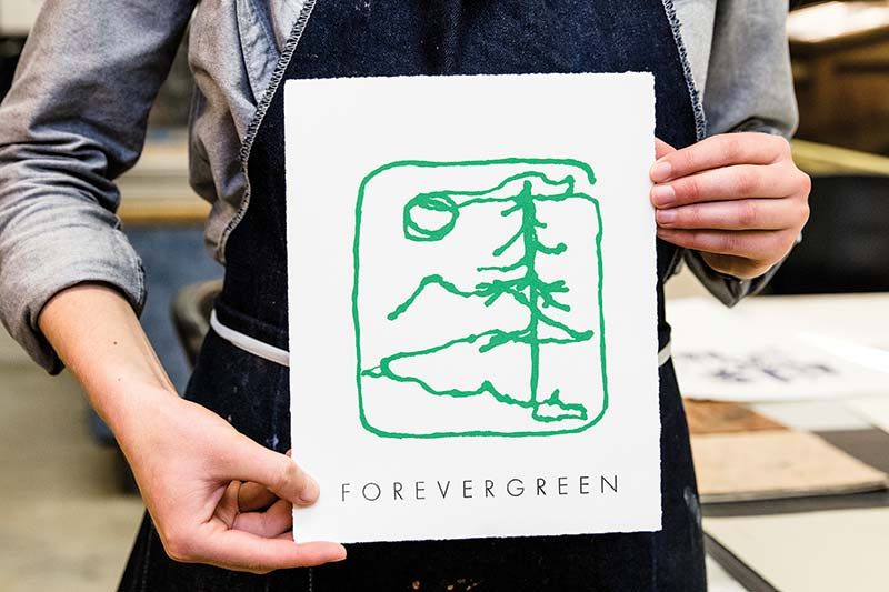 "Letterpress print features tree mark from the school logo and the word ""Forevergreen."""