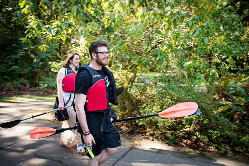Students carry kayak paddles with them