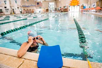 A person rests in between laps in the pool.