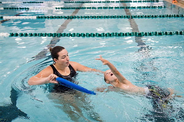A child learns to swim with the help of a coach and a boogie board.