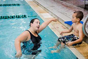 Swim instructor demonstrates strokes to student.