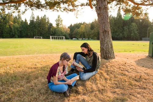 Two students read books under a tree beside the soccer fields