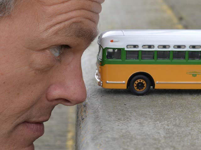 Stokeley looking into the windsheild of a small toy city bus