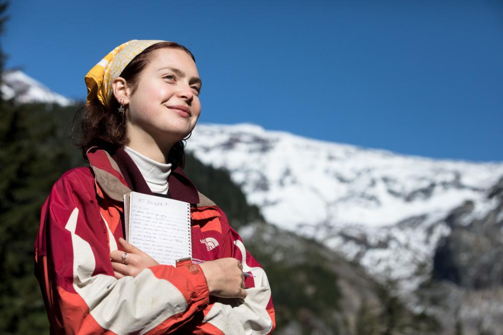 A smiling student poses with a notebook in front of Mt. Rainier