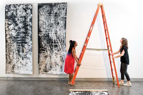 Carol Williams setting up an art display