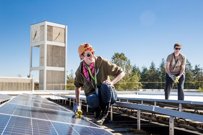 Student groups take on service projects at a variety of sites both on and off-campus for the annual Community to Community Day of Action on Weds., Sept. 19, 2018. Cleaning the solar panels on the roof of the Library building.