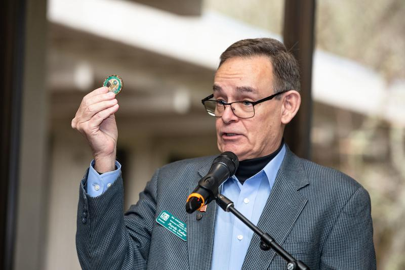 Randy Kelley, director of the Veterans Resource Center, hold up a challenge coin as he hosts the 2019 Veterans Challenge Coin Ceremony on Weds., Dec. 18, 2019