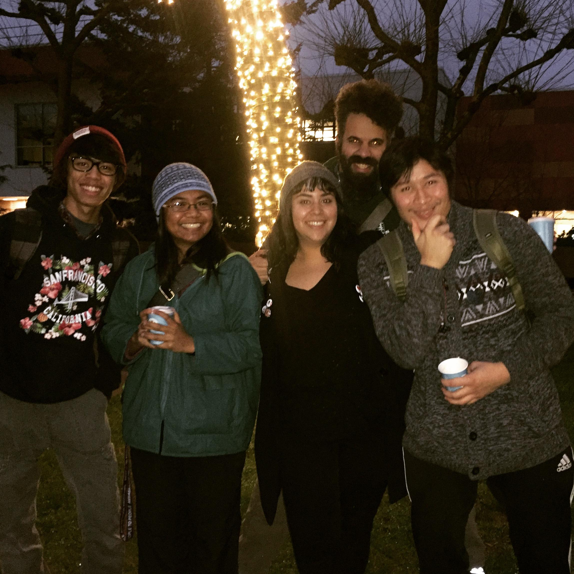TRiO students smile in front of tree-lighting at the the annual Winter Tree-Lighting Celebration on Red Square.