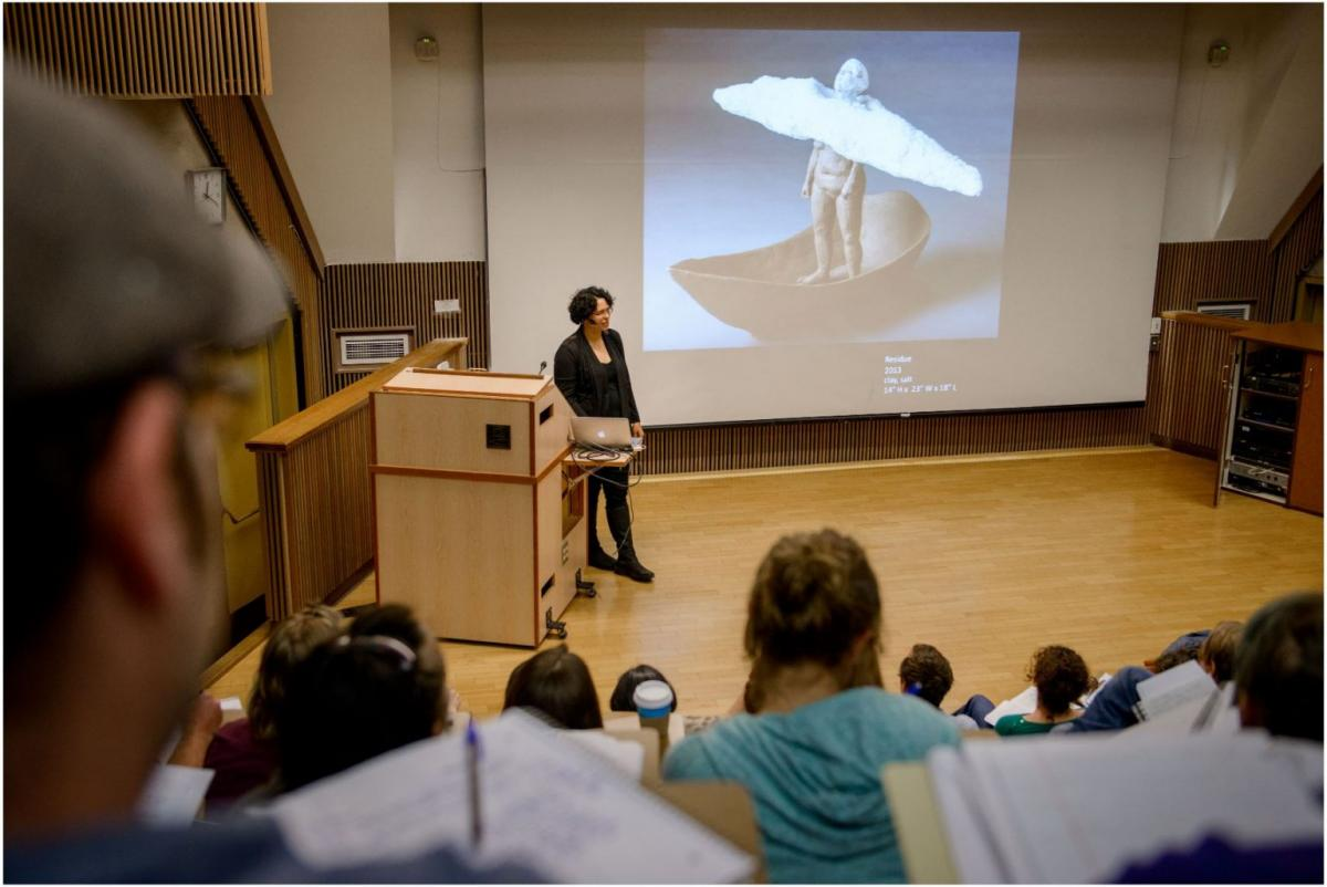 An artist lectures in front of a projection screen in a lecture hall