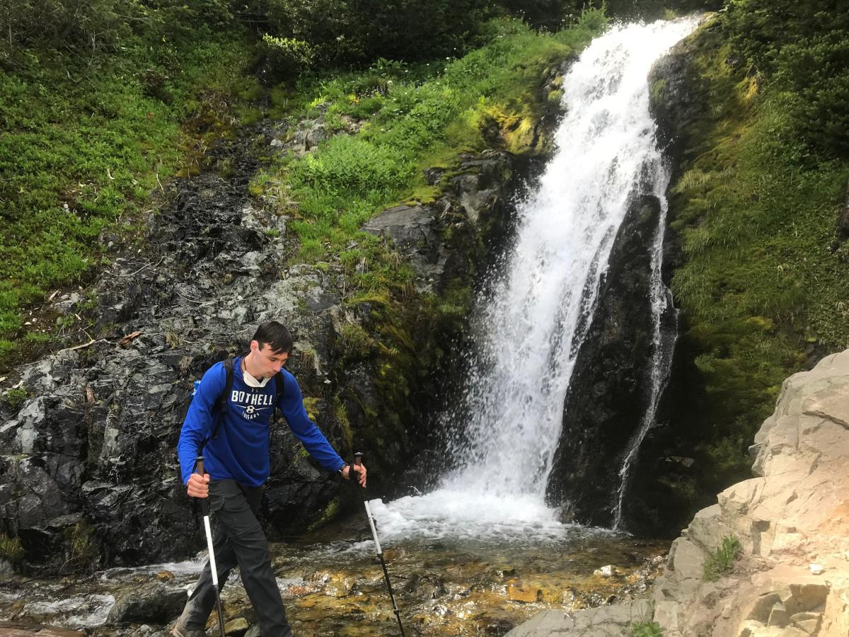 Arlo, a student ambassador out mountain hiking by a waterfall.