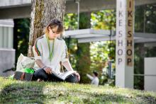 Evergreen student reading handbook under tree on campus